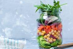 Salade verte avec des couches de saumons, d'avocat et de pois chiches dans le pot Photos stock
