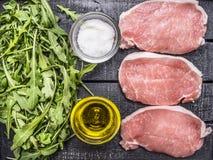 Salade verte d'arugula avec le pétrole et le sel avec la fin rustique en bois de vue supérieure de fond de bifteck cru de porc  Photo libre de droits