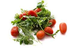 Salade verte d'arugula et tomates rouges sur le fond blanc Images libres de droits