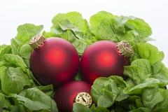 Salade verte fraîche avec trois boules de Noël de rouge Images libres de droits