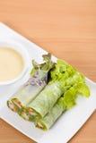 Saladebroodjes en roomsaus op witte plaat en houten lijst stock foto's