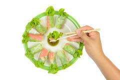 Saladebroodjes met de eetstokjes die van de handgreep in zeevruchtensaus onderdompelen stock foto