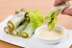 Saladebroodjes op hand Witte plaat Houten lijst stock afbeelding
