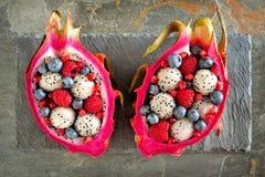 Salades de fruit du dragon avec des baies au-dessus d'ardoise photo stock