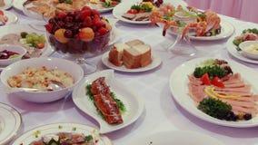 Salades, vlees, vissen, fruit, aardbeien op lijst stock videobeelden