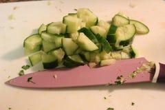 Saladevoorbereiding - het snijden komkommer in stukken Stock Fotografie