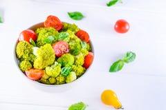 Saladier avec les tomates-cerises, le brocoli bouilli, le basilic et les ingrédients frais sur le fond en bois blanc Mode de vie  Image libre de droits