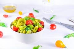 Saladier avec les tomates-cerises, le brocoli bouilli, le basilic et les ingrédients frais sur le fond en bois blanc Mode de vie  Photo libre de droits
