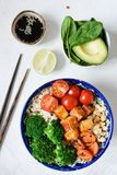Saladier végétarien sain avec le tofu, le brocoli, le riz et l'avocat sur le fond blanc Photos libres de droits