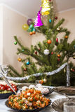 Salads and appetizers. Banquet in the restaurant. Focused on one dish. Against the background of Christmas trees with toys. Stock Images