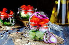 Salads of fresh tomatoes,cucumbers in glass jars Stock Photos