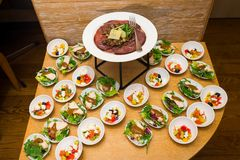 Salads with fresh vegetables and meat with sauces. A variety of cheese varieties and meat delicacies next to the table with salads and other fresh sliced royalty free stock photo