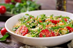 Salads with quinoa, arugula, radish, tomatoes and cucumber stock images