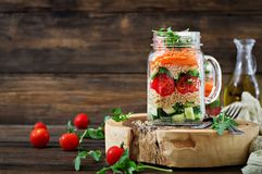 Salads with quinoa, arugula, radish, tomatoes and cucumber in glass stock photo