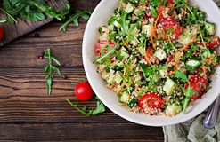 Salads with quinoa, arugula, radish, tomatoes and cucumber. In bowl on wooden background. Healthy food, diet, detox and vegetarian concept. Top view. Flat lay stock photos