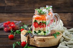 Salads with quinoa, arugula, radish, tomatoes and cucumber. In glass jars on wooden background. Healthy food, diet, detox and vegetarian concept royalty free stock photos