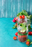 Salads with quinoa in jars. Salads with quinoa, couscous, spinach, radish, tomatoes and zucchini in glass mason jars, standing with fresh vegetables over bright Stock Photo