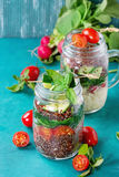 Salads with quinoa in jars. Salads with quinoa, couscous, spinach, radish, tomatoes and zucchini in glass mason jars, standing with fresh vegetables over bright Stock Photos