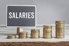 Salaires de signe avec des piles de pièce de monnaie de croissance Photographie stock libre de droits