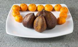 Salak果子和柑桔普通话在白色板材 免版税库存照片