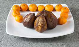 Salak Fruit and clementines mandarin on white plate. Salak Fruit and clementines mandarin Royalty Free Stock Photos