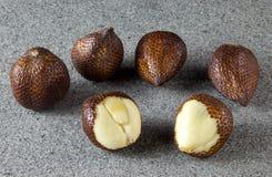 Salak Fruit peeled on grey stone. Group of Salak Fruit peeled on grey stone Royalty Free Stock Photos