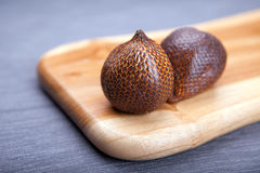 Salak or snake fruit in a wooden board Stock Photos