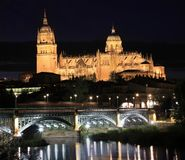 Salamanca skyline at night and Enrique Esteban Bridge over Tormes River stock photo