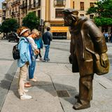 Woman looks at a bronze statue, Adares by Agust n Casillas, in the historic centre of Salamanca, Castilla y Leon, Spain. Salamanca, Spain - June 12, 2018: Woman royalty free stock photos