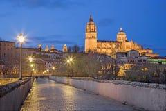 SALAMANCA, SPANIEN: Der Kathedrale und Brücke Puente-Romano über dem Rio Tormes-Fluss an der Dämmerung Stockbild