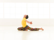 Salamba kapotasana. Colorful dressed male repeating salamba kapotasana yoga exercises in a white room with window background Royalty Free Stock Image
