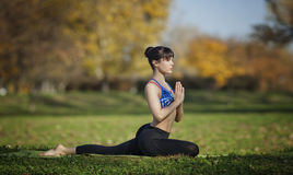 Salamba kapotasana yoga pose. Young woman practicing yoga outdoors Royalty Free Stock Photo
