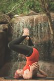 Salamba Sarvangasana. Woman practicing yoga near waterfall. Shoulder Stand. Salamba Sarvangasana. Toned Royalty Free Stock Images