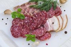Salame, bacon e verdi su un fondo bianco Fotografie Stock