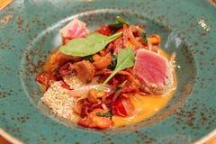 Salame, cogumelos e atum fritados na tabela do restaurante imagem de stock