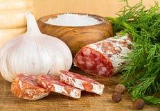 Salame cortado na placa de corte, com aneto, pimenta, sal Foto de Stock Royalty Free