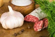 Salame découpé en tranches sur la planche à découper, avec l'aneth, poivre, sel Image libre de droits