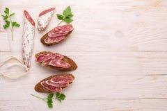 Salame e pane su fondo di legno bianco Vista superiore fotografia stock