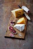 Salame espanhol, brie e queijo duro em uma placa de madeira Fotos de Stock Royalty Free