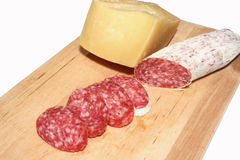 Salame and fromage. A sliced italian salami on wood with cheese stock photos