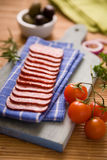 Salami. Pieces on a wooden cutting board Royalty Free Stock Photo