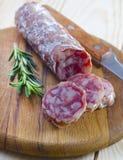 Salami. With fresh rosemary on wood royalty free stock photo