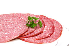 Salami. Slice of salami with parsley isolated stock images