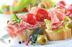 Salami appetizers. Delicious appetizers with Italian salami, lettuce leaves and cherry tomatoes on slices of baguette Stock Photos