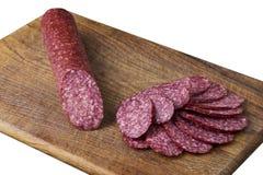Salami auf einem Ausschnittvorstand Stockfotos