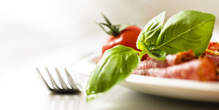Salami with basil and tomato Royalty Free Stock Photography