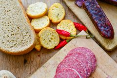 Salami and bread. Bread slices and Bruschetta with different kinds of Salami , peperoncino, fresh onion and spices as a rustic lunch royalty free stock photo