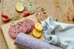 Salami and bread. Bread slices and Bruschetta with different kinds of Salami , peperoncino, fresh onion and spices as a rustic lunch royalty free stock photos