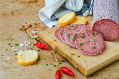 Salami and bread. Bread slices and Bruschetta with different kinds of Salami , peperoncino, fresh onion and spices as a rustic lunch stock images