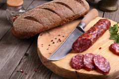 Salami, bread and a knife on the  table Stock Image